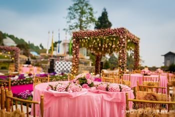 Photo of A pink themes wedding with a floral mandap in the background