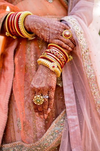Photo of beautiful bridal hands with kadas and enamel ring