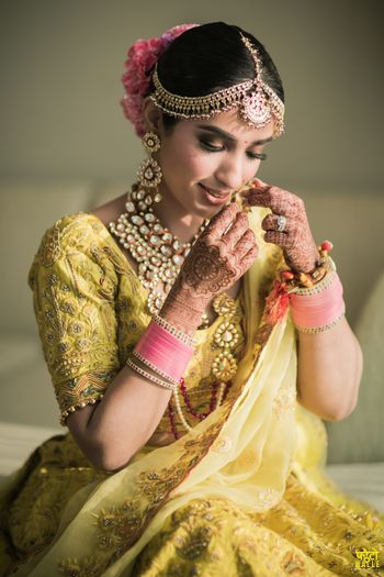 Photo of A bridal portrait captured as the bride shyly gets ready