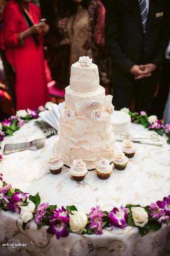 Photo of White wedding cake with cupcakes