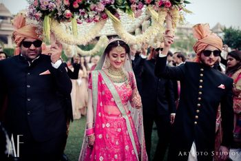 Bride entering under unique phoolon ki chadar