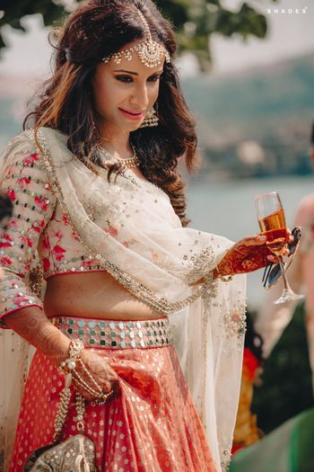 A bride in a pastel-colored mehndi outfit enjoying champagne