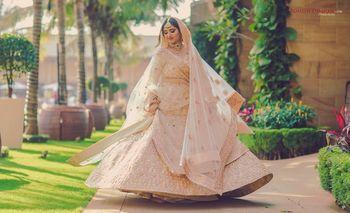 Photo of Twirling bride in light peach lehenga