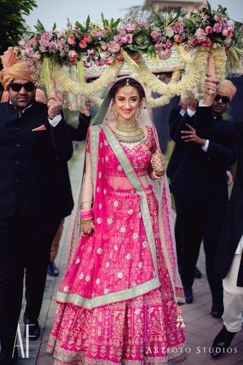 Photo of Bride in bright pink entering under pretty phoolon ki chadar