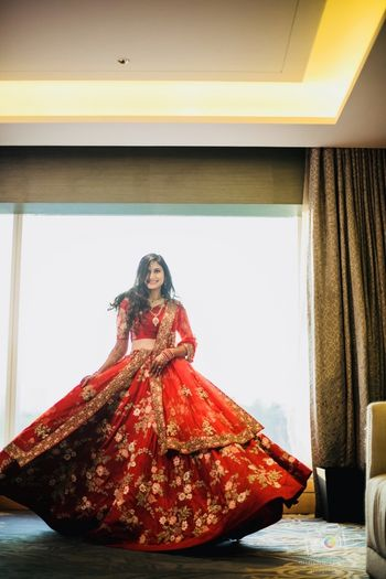 Bride twirling in red Shyamal bhumika lehenga