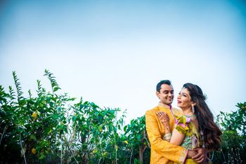 A bride and groom to be in yellow pose at their mehendi ceremony