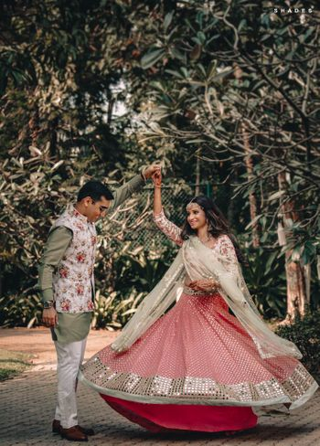 Photo of A bride in a sequinned pink lehenga twirling with her husband