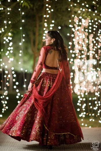 Maroon sangeet lehenga with sheer sleeves and deep cut back