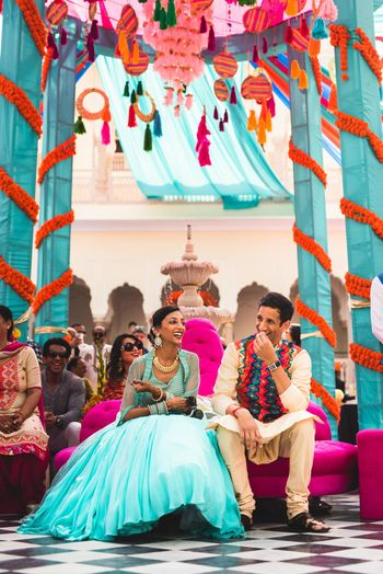 Photo of A couple sits under a colorful tent setup for the mehndi