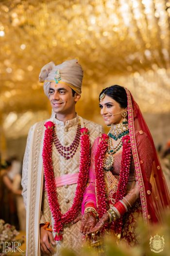 Photo of contrasting bride and groom outfits wearing red jaimalas