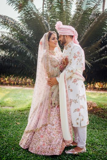 Matching bride and groom in light pink floral outfits