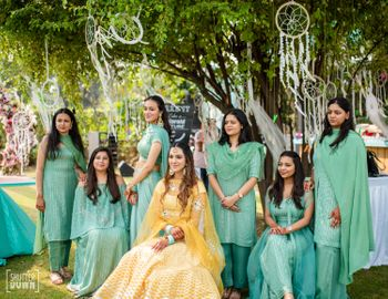 bride with bridesmaids in matching outfits on mehendi