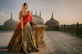 A bride dressed in green and red lehenga on her wedding day