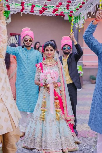 Photo of A bride in powder blue lehenga enters with a bouquet in hand.