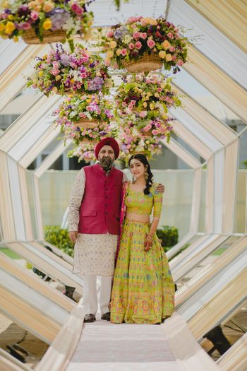 Photo of Bride posing with father on mehendi