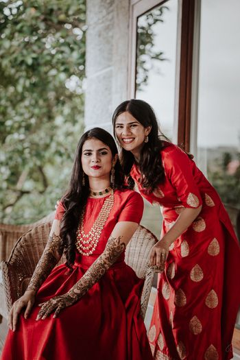 Photo of bridal mehendi look with bride to be matching with her sister in red