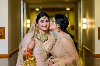 Photo of Bride with sister kissing her