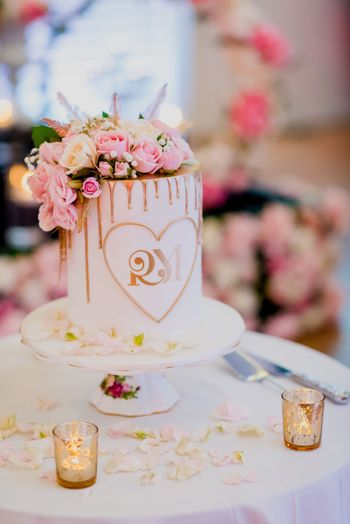 White and pink wedding cake with flowers and monograms