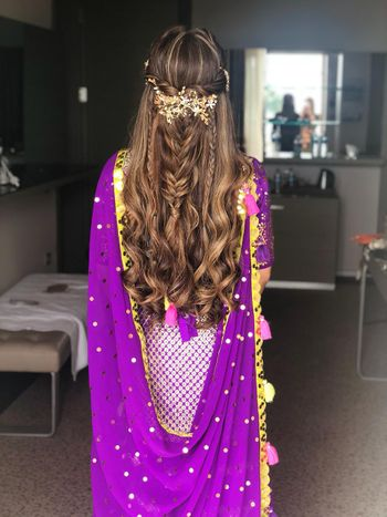 Pretty mehendi hairstyle with wavy hair and accessory