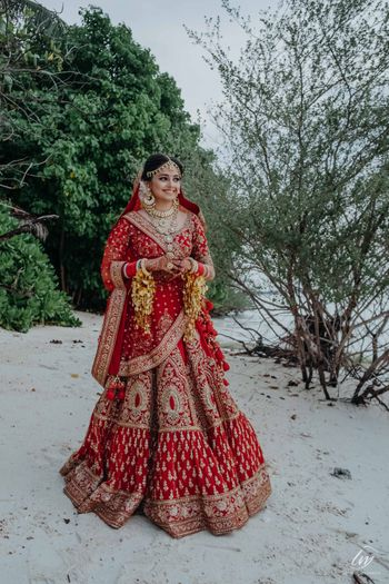 bride in red posing on beach before the wedding