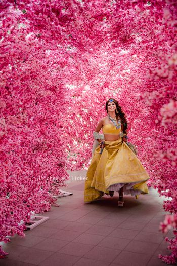 A bride in a yellow lehenga for her mehndi with floral jewellery