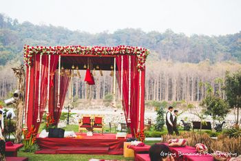 Photo of red beautiful rustic mandap with roses and flowers against jungle backdrop