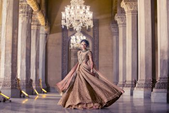 Bride twirling in gold bridal lehenga