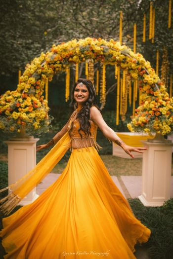 Photo of Bride twirling in yellow mehendi lehenga