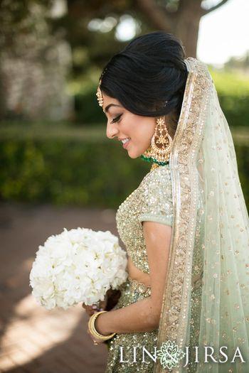 Photo of Shy bride portrait in light green lehenga