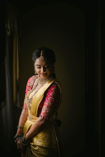 Photo of Bride posing in yellow kanjeevaram saree with an embroidered pink blouse.