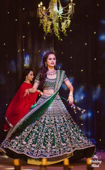 Bride dancing on sangeet in dark green lehenga