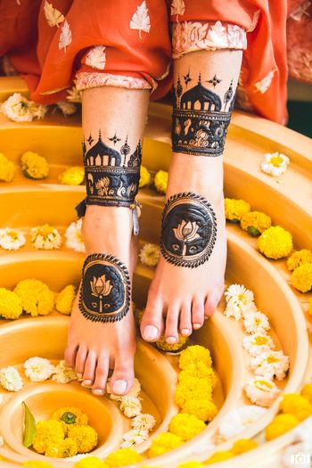 Feet Mehendi design with lotus motifs & tomb-like structures.