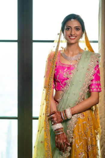 A bride dressed in a yellow and pink lehenga at her wedding