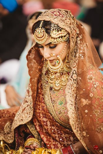 Photo of A bride wearing stunning gold jewelry in vintage designs