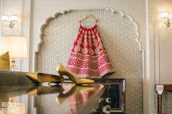 Photo of Bridal lehenga in red on a hanger in the room