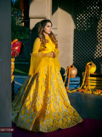 A picture of a bride to be dressed in yellow lehenga