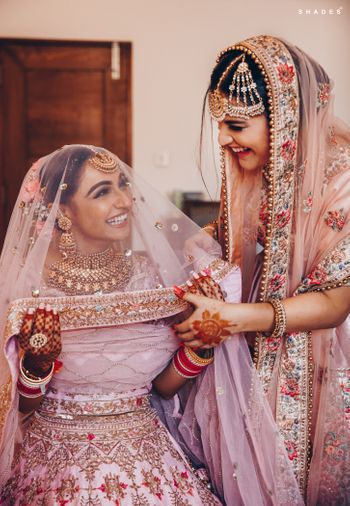 Photo of A bride getting ready with the help of her sister