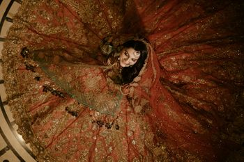 Bride sitting on the floor with her lehenga flared out.