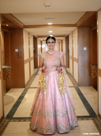 Light pink bridal lehenga with silver work and scalloped edge