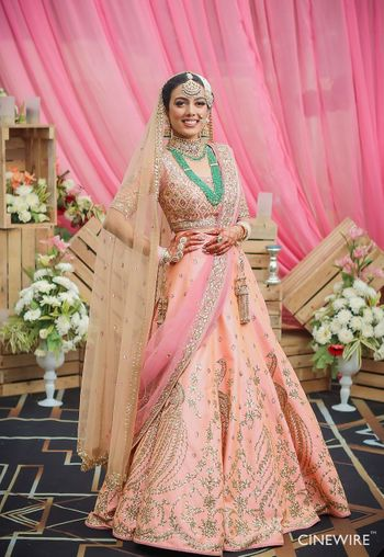 Bride in bright peach lehenga with green necklace