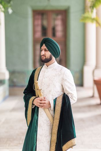 Photo of Sikh groom with velvet stole and sword