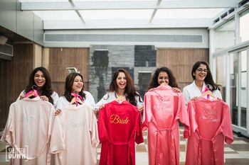 Photo of Bride with bridesmaids holding up personalised robes