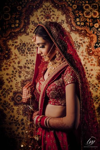 Photo of pretty wedding day bridal portrait in red lehenga