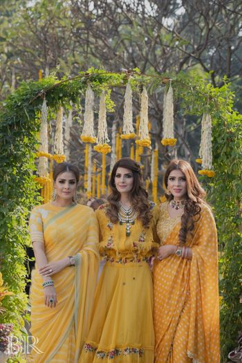 bride and her sisters in matching yellow outfits on mehendi