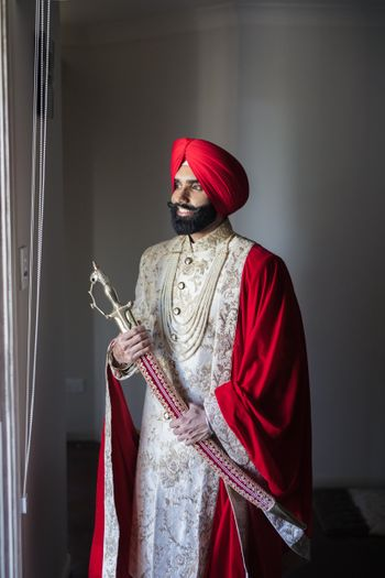 A groom dressed in a white sherwani with red turban and red shawl