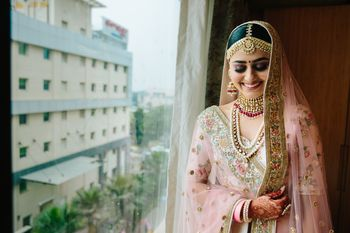 Photo of A bride in a soft pink lehenga and gold jewelry