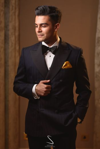 Photo of groom in black tux with gold pocket square