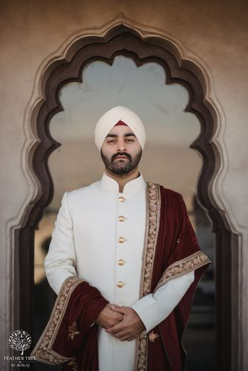 Off white sherwani with maroon velvet dupatta