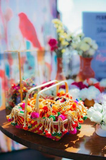 Mehendi favour ideas with pompom jewellery on display