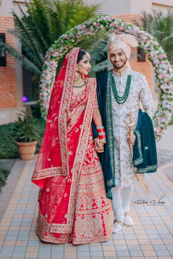 Photo of groom sherwani in white and green with bride in red